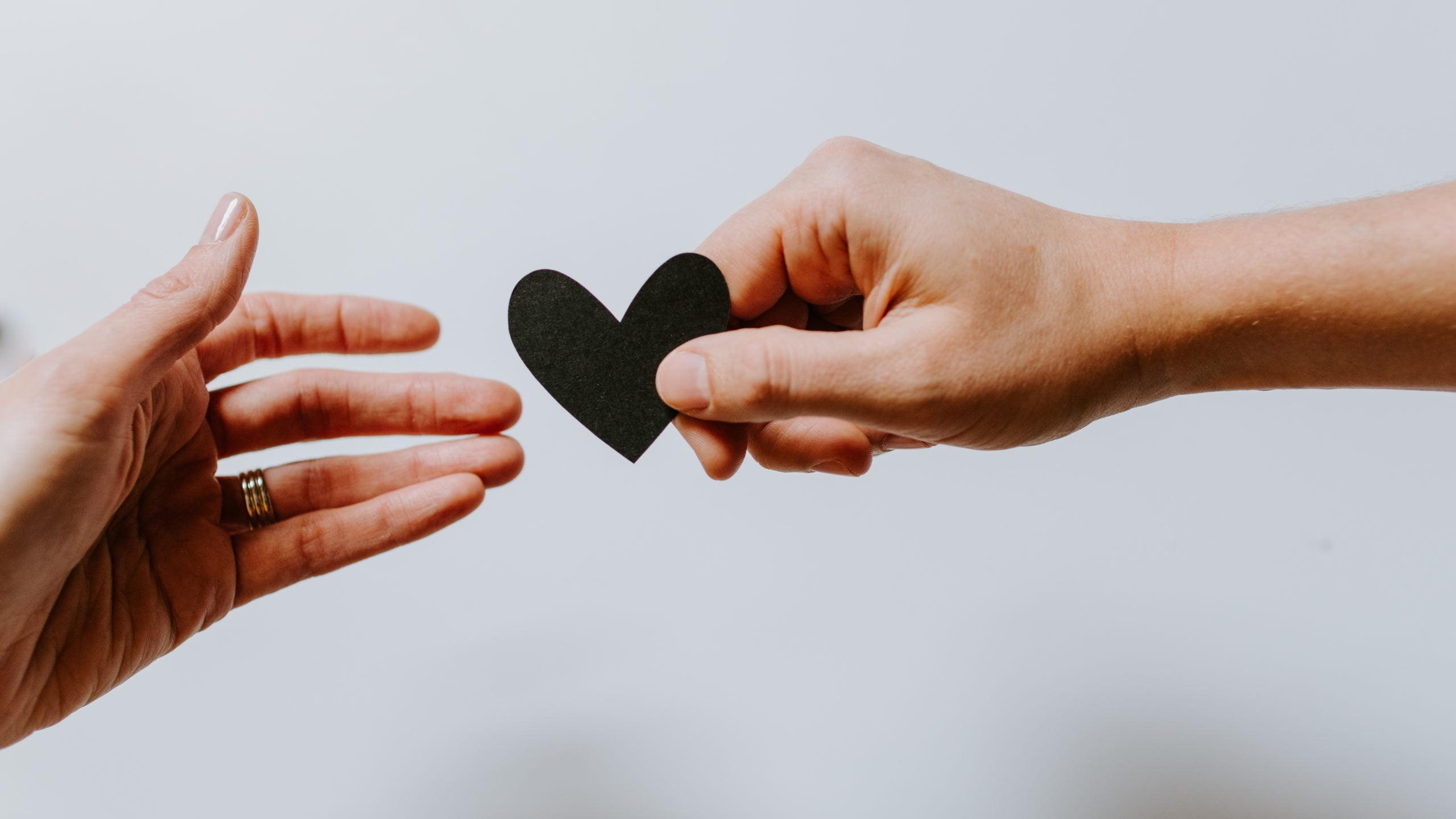 man handing a woman a heart shape stock unsplash